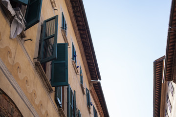 View looking up at widow shutters opened and closed in narrow streets of small town Italy