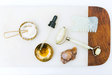 Facial oil serum in gold dish with eyedropper, creamy lotion with spoon, jade roller, crystal, and gua sha close up on white marble background with wood edge / green natural holistic beauty concept