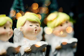 Christmas caroling or Carolers singing outside with snows.Angel group singing carol song on...