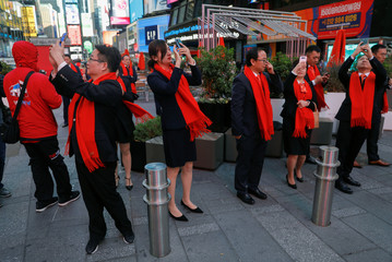 Executives with FangDD runs take pictures Times Square as company holds IPO at Nasdaq Market Site in New York