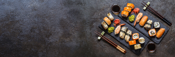 Fotobehang Sushi bar sushi rolls with rice and fish, soy sauce on a dark stone background