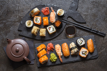 Foto op Aluminium Sushi bar sushi rolls with rice and fish, soy sauce on a dark stone background