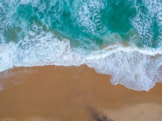 Sand beach aerial, top view of a beautiful sandy beach aerial shot with the blue waves rolling into the shore