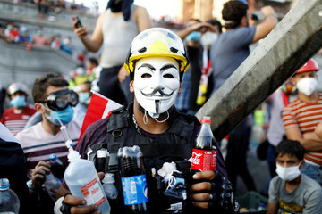 An Iraqi demonstrator caries bottles of soda used to neutralise tear gas during an anti-government protest in Baghdad