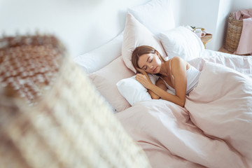 Relaxed young female person sleeping in soft bed
