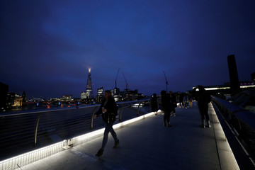 People cross the Millenium Bridge with a night scene of City of London in the background, in London