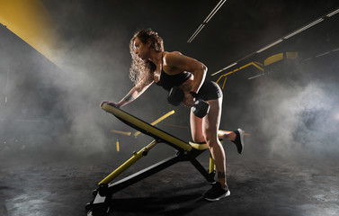 Athletic girl does exercises using sports equipment in a gym.