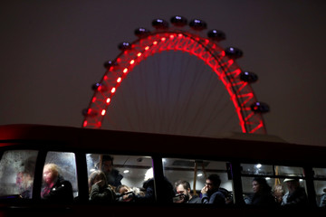 People are seen on the bus crossing Westminster Bridge with the London Eye in the background, in London