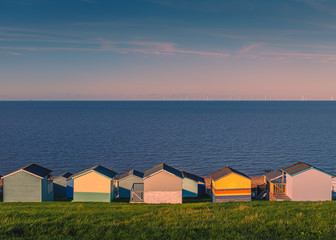 Colourful beach huts along a grass verge in Tankerton, Whitstable, Kent, UK. The sea and sky are blue on a sunny winter day, late in the afternoon. The wind farm can be seen on the horizon