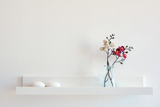 Composition of dried flowers on white wall background.