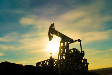 Oil pump on a sunset background. Oil production, fuel, natural resources.