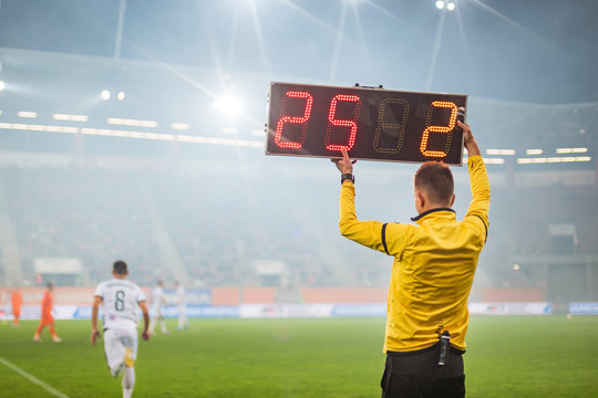 Technical referee shows players substitution during soccer match.