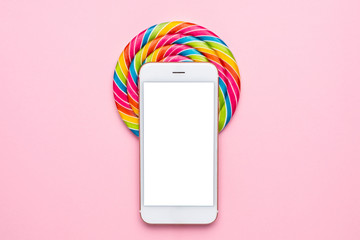 Colorful lolipop and mobile phone on pink background, techology and children sweets