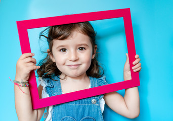Portrait of cute little girl holding a picture frame on blue background