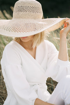 Blond young woman in dunes wearing white wrap blouse and summer hat
