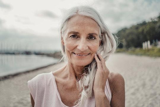 Portrait of senior woman standing on beach