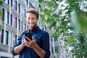Smiling young businessman using mobile phone in the city Wall mural