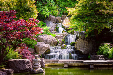 Foto op Canvas Zen Waterfall long exposure with maple trees and bridge in Kyoto Japanese green Garden in Holland Park green summer zen lake pond water in London, UK