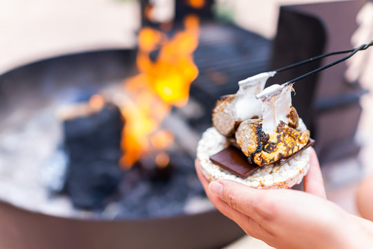 Young woman hand holding gooey roasted charred marshmallows smores with chocolate and rice cake cracker by fire in campground campfire grill