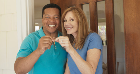 older couple holding the keys to their new house while standing at front door