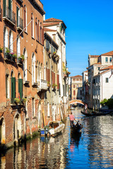 Fototapete - Gondola sails past vintage houses, Venice, Italy. Sunny view of old street in the Venice center. Romantic water trip across Venice city in summer. Scenery of narrow canal in Venice on sunny day.