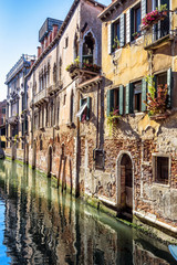 Fototapete - Vintage houses, Venice, Italy. View of facades of residential buildings on old street in Venice center. Romantic water trip across Venice city in summer. Scenery of narrow canal in Venice on sunny day