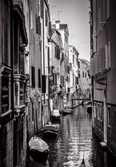 Fototapete - Old houses with moored boats, Venice, Italy. Vertical view of narrow street in black and white. Vintage architecture of Venice in summer. Scenery of small canal in the Venice city.