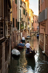 Fototapete - Gondola sails past vintage houses, Venice, Italy. Vertical view of old street in the Venice city. Romantic water trip across Venice in summer. Scenery of narrow canal in the Venice center.