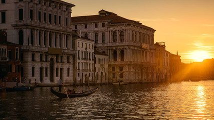 Fototapete - Venice at sunset, Italy. Gondola with tourists sails on Grand Canal at night. Panorama of Venice city in evening light. Scenery of sunny street in the Venice center. Romantic water trip at dusk.