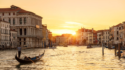 Fototapete - Venice at sunset, Italy. Gondola with tourists sails on Grand Canal at night. Panorama of Venice city in evening sunlight. Scenery of sunny street in the Venice center. Nice urban landscape at dusk.