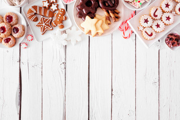 Christmas cookie top border. Above view table scene over a white wood background with copy space....
