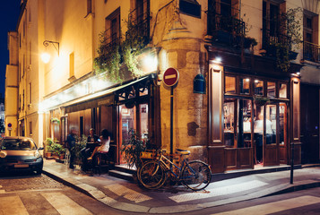 Aluminium Prints Bicycle Night view of cozy street with tables of cafe and old bicycle in Paris, France