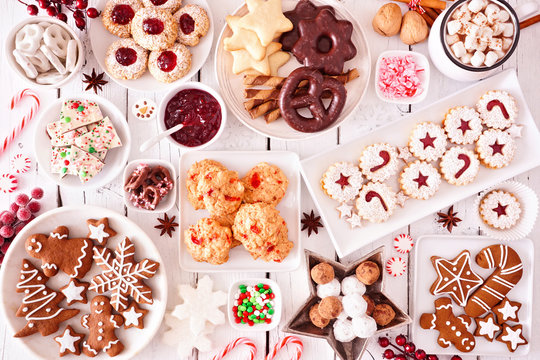 Christmas sweets and cookies. Top view table scene over a white wood background. Holiday baking concept.