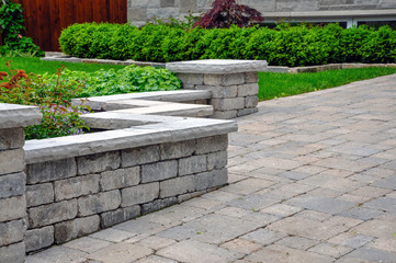 A seat wall with pillars and natural stone coping helps define a tumbled paver driveway and is a beautiful landscaping feature.