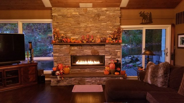 Cozy Home with Beautiful, Large Stone Masonry Fireplace in Subtle Earth Tones, Lit at Dusk, Inside a Lodge Style Home; Masonry at its Best
