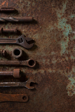 Flat lay rusty tools on rusted old metal table.