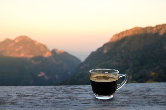 Hot americano coffee on wooden table with mountain view
