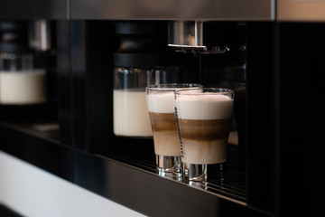 Two cups with cappuccino in a coffee machine