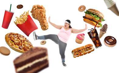 Overweight Asian woman fighting off junk food isolated on white background
