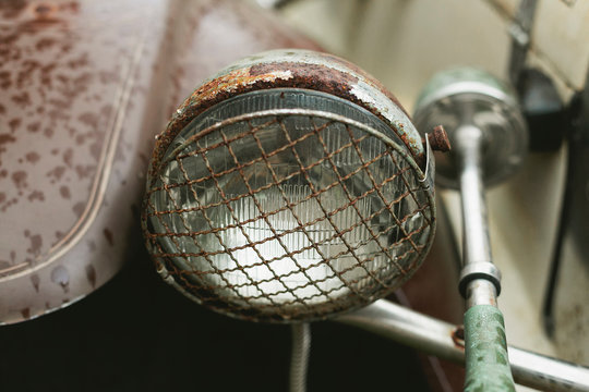 Top view of rusted vintage car headlight with protective metal grill cover