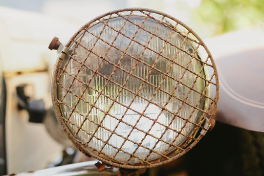 Vintage car headlight with rusted grill cover