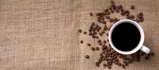 cup of coffee and coffee beans on jute
