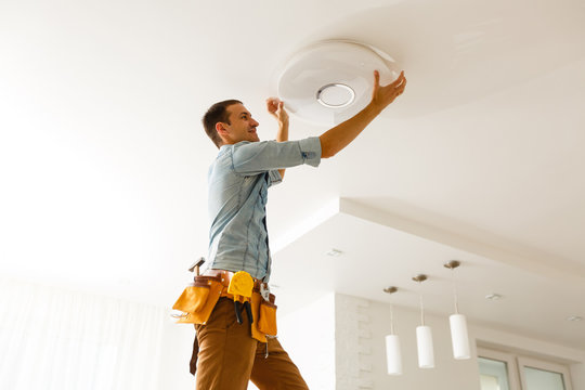 Electrician is installing and connecting a lamp to a ceiling.