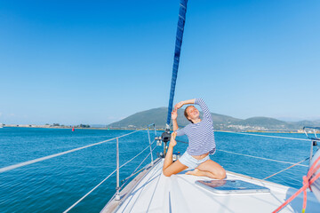 Girl is practicing yoga on the deck of the yacht boat