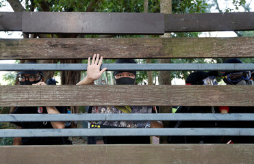 "A protester waves hand behind a fence during a march billed as a global ""emergency call"" for autonomy, in Hong Kong"