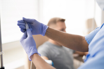 Hands of gloved doctor holding part of dropper with medicine for one of patients