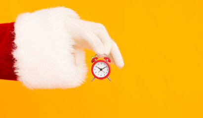 Santa hand holding small red alarm clock with time on orange