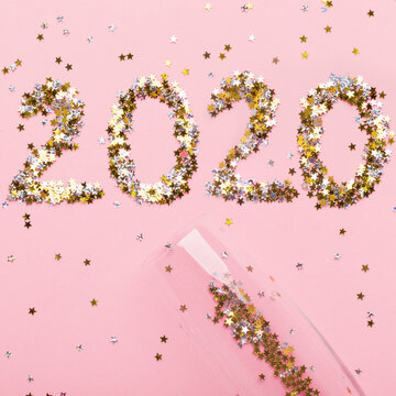 Big 2020 letters and champagne on pink background