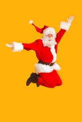 Happy Santa claus jumping on orange background