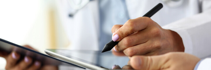 Female GP making electronic notes in tablet pc Wall mural